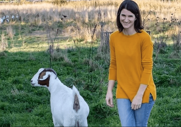 Emma Smalley pictured in a field with one of her goats
